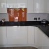 Luxury Handle Less Fitted Kitchen With Solid Worktops & Coloured Glass Splashback